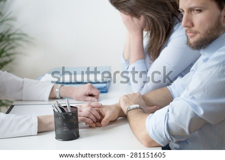 Young broken down couple at physician's cabinet - stock photo
