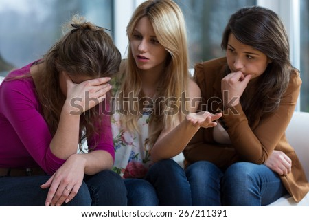 Young broken down woman and her helpful friends - stock photo