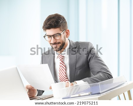 Young broker working with laptop, while analyzing data at office.  - stock photo