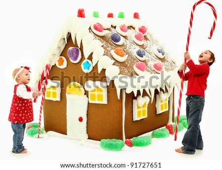 Young brother and sister building a giant gingerbread house together. - stock photo