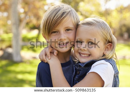 Young brother and sister embracing in a park look to camera
