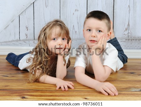 young brother and sister laying together in floor with hands on chin - stock photo
