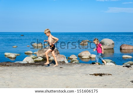 Young brother and sister running on the beach alongside the ocean and small rocks as they enjoy their summer vacation on the beach - stock photo