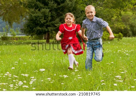 young brother and sister running through a green grassy field with smiles on their faces. - stock photo