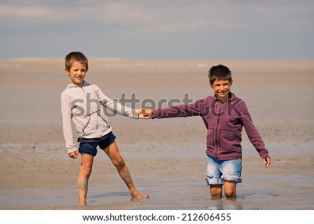 Young brothers having fun with quicksand on the beach in front of Mont Saint Michel ancient village. Normandy, France.