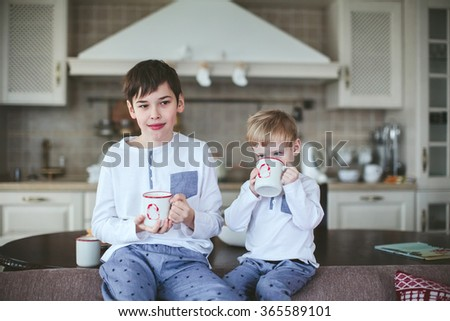 young brothers in identical pajamas holding mugs of milk sitting on a sofa in the dining room - stock photo