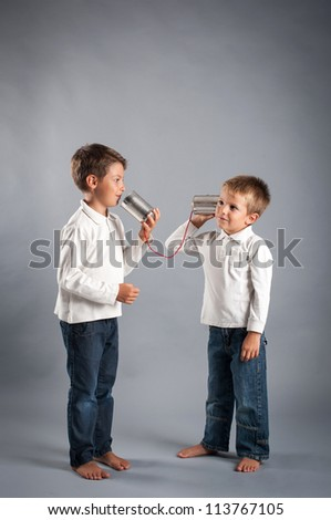 Young brothers talking with tin can telephone. - stock photo