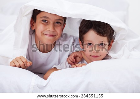Young brothers together - boys under the blanket - stock photo