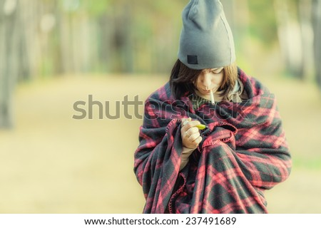 Young brown hair woman in wrap with cigarette and lighter - stock photo