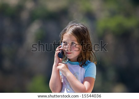 Young Brown Haired Child using Phone - stock photo