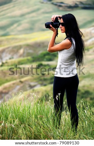 Young brown haired woman photographing in Tuscany - stock photo