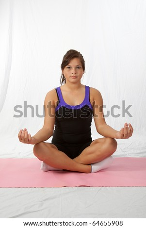Young brunette aboriginal woman sitting crossed legged in lotus position doing yoga on pink mat