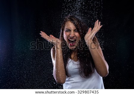 Young brunette and drops of water on black background