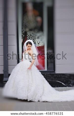 Young brunette bride wearing white dress walking street - stock photo