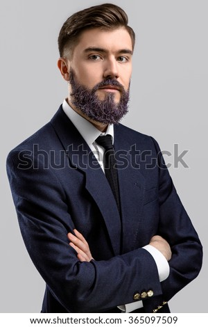 Young brunette businessman, with violet beard, wearing in dark blue suit and tie, posing with crossed hands, on gray background, in studio, waist up - stock photo