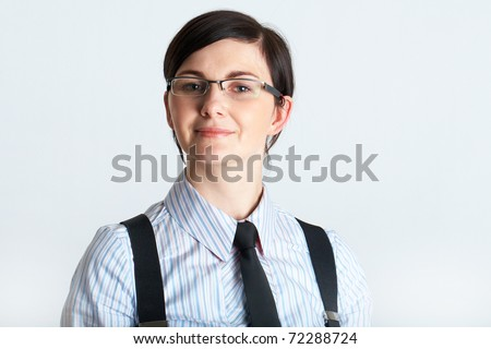 young brunette businesswoman in shirt and necktie, studio shoot on grey background
