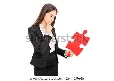 Young brunette businesswoman looking at a big red piece of a puzzle isolated on white background - stock photo
