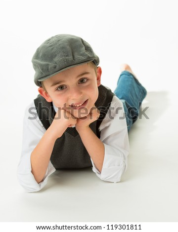 Young brunette caucasian boy laying on stomach with flat cap - stock photo