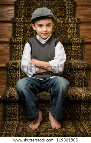 Young brunette caucasian boy sitting on stairs with flat cap - stock photo