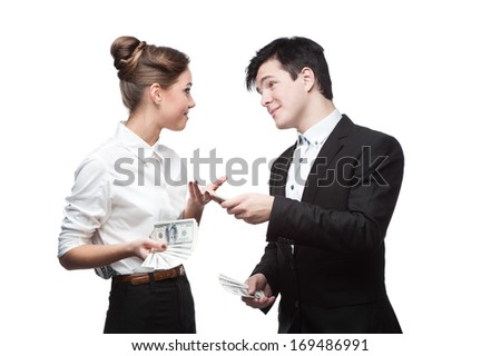 young brunette caucasian businessman giving a lot of dollars to surprised smiling business woman - stock photo