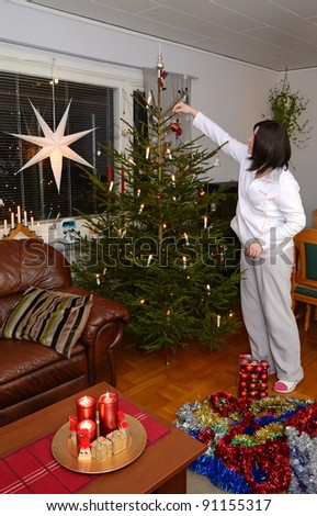 Young brunette decorating Christmas tree
