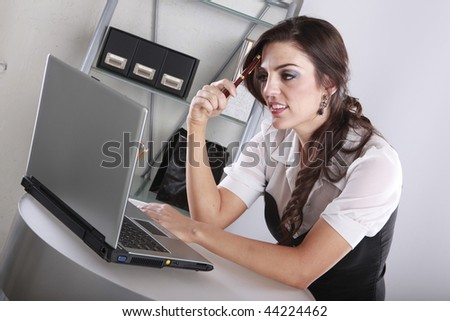 Young brunette examining data at her contemporary office