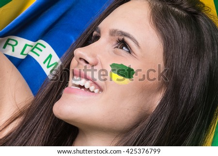 Young brunette fan celebrating with the flag of Brazil - stock photo