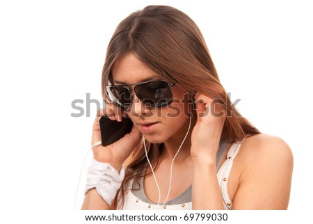 Young brunette fashion spy woman in sunglasses enjoy listening to music in white earphones and talking on new mobile cellphone isolated on a white background - stock photo