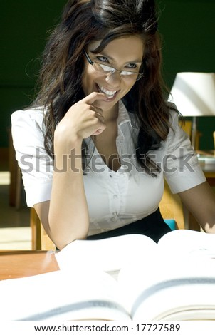 Young brunette female smiling at the camera while in the library� - stock photo