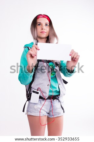 Young brunette female student standing and listening to music from your device. Beautiful young backpacker holding empty white board - stock photo