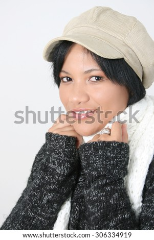 Young brunette female wearing a hat with scarf wrapped around her  - stock photo