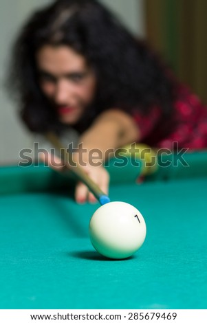 Young brunette girl aiming to ball playing billiard game. Close up image of ball with selective focus. Billiard blurred background. - stock photo