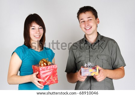 young brunette girl and man holding gifts and smiling - stock photo