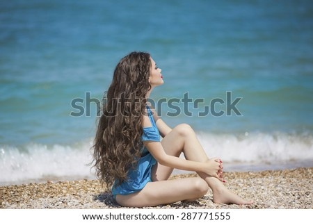 Young brunette girl enjoying and sunbathing on the beach with long wavy hair in blue bikini - stock photo