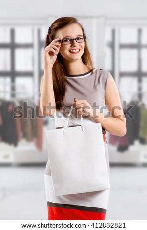Young brunette girl in glasses with white shopping bag in clothing store - stock photo