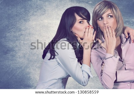 Young brunette girl is whispering in her friend's ear. Gossip conceptual - stock photo