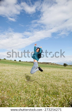 Young brunette girl jumping in a field full of flowers - stock photo