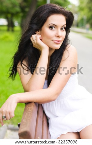 Young brunette girl relaxing in a park - stock photo
