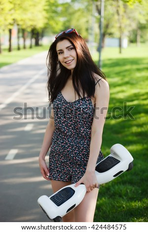 Young brunette girl riding electric mini hover board scooter in green park. Good summer weather, ecological urban transportation technology and pretty model - stock photo