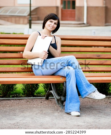 Young brunette girl sitting on a sunny day on a bench in the park with laptop in her hands - stock photo