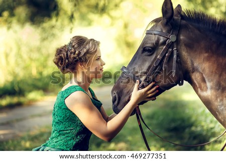 Young brunette girl wears long green dress looking at brown horse in the park.