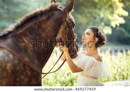 Young brunette girl wears long white dress looking in horses eyes in the summer park.