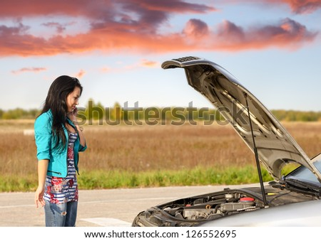 young brunette girl with   broken down car with   hood open call for help - stock photo