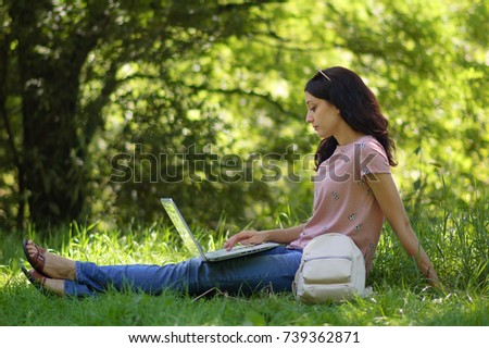 young brunette girl with laptop outdoors is working