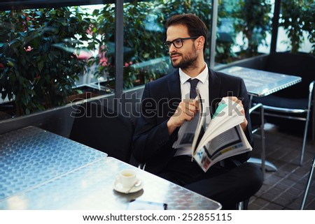 Young brunette hair businessman holding a newspaper outdoors at a coffee shop with cup of coffee on the table  - stock photo