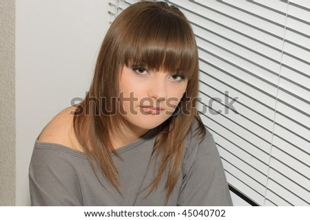 Young brunette in a gray dress sitting home on the windowsill - stock photo