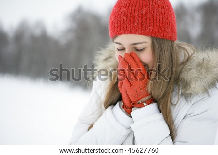 Young brunette in a park in winter sneezes. Closes mouth with her hands - stock photo
