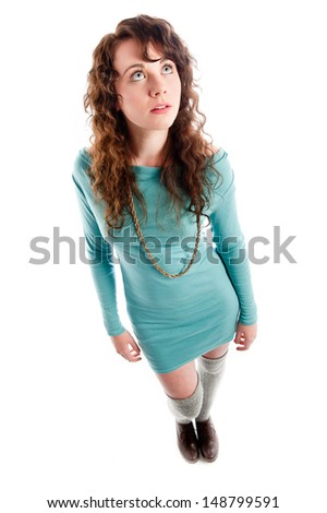 Young brunette in a turquoise dress posing in the studio