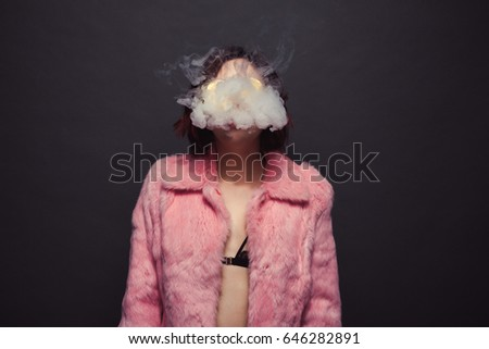 Young brunette in black bra and pink fur coat breathing out smoke on black background.