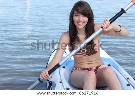 Young brunette in paddle boat - stock photo